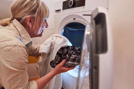 Housewife in front of tumble dryer or washing machine in the bathroom for cleanliness and hygiene