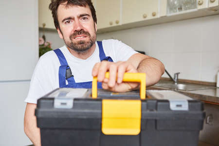 Man as a craftsman from the plumber's emergency service with tool box in the kitchen Imagens