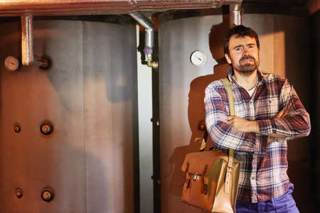 Handyman with arms crossed after DIY maintenance of heating in basement