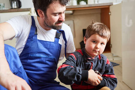 Child as a craftsman trainee with spare parts helps father to assemble it at the kitchen sink