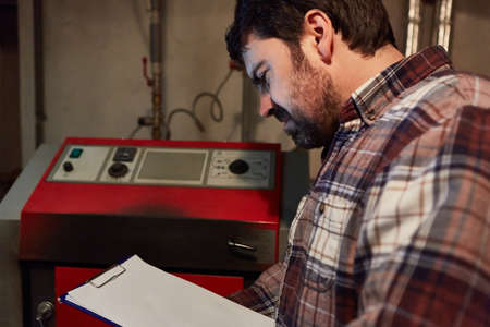 Heating installer with checklist for maintenance of the gas heating in the boiler room Imagens