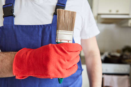 Painter or varnisher with paintbrush as a symbol for craft and renovation