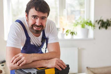 Smiling handyman or handyman draws on his toolbox