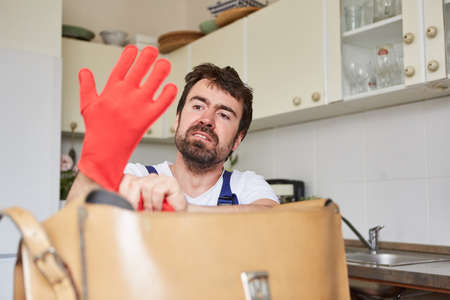 Do-it-yourselfer puts on rubber gloves to repair the drainpipe