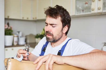 A handyman or plumber is looking for a spare part for a repair