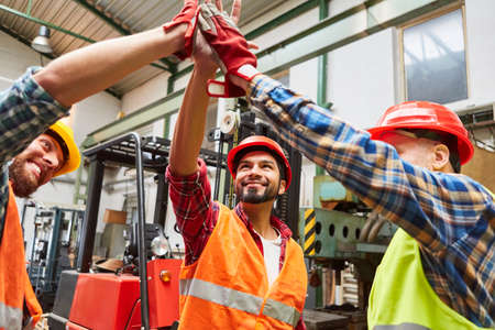 Flu happy warehouse worker in warehouse makes high five for motivation in front of forklift truck