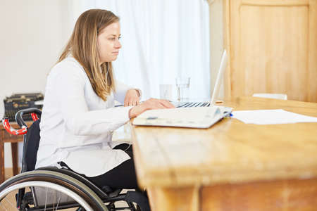 Paralyzed business woman in wheelchair working on computer online in home office in living room