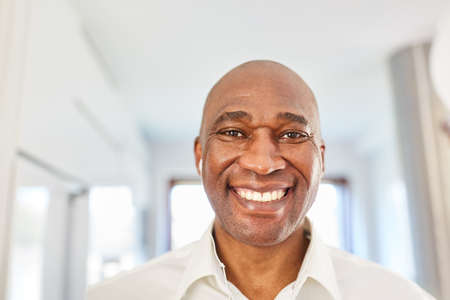 Portrait of a happy african man with in-ear headphones at home or in the home office Stock Photo