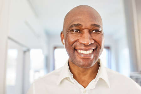 Smiling African Business Man With In-Ear Headphones At Home In The Home Office