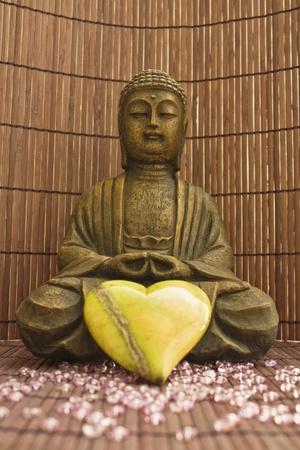 oneness: scultura del Buddha con un cuore verde