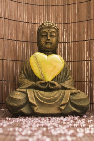 buddha sculpture with a green heart