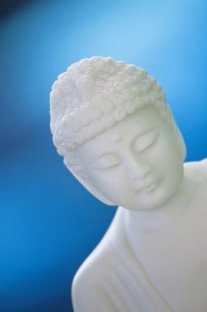 bue: white buddha sculpture on bue background