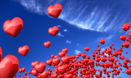 Red hearts flying against a blue sky