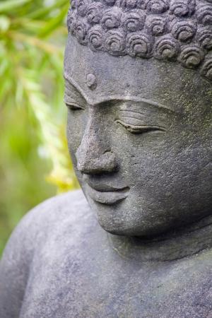 position d amour: Bouddha en pierre dans le jardin Banque d'images