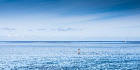 reisen: Person mit paddelboard auf dem Meer