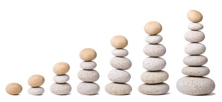 Seven Stacks of Stones on a white Background - a nice Zen-like Background Stock Photo