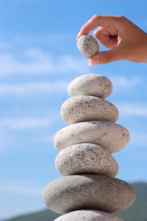 Summer. Wild beach. Someones hand constructs equilibrium. Stock Photo