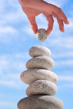 Verão. Praia selvagem. A mão de alguém constrói equilíbrio.