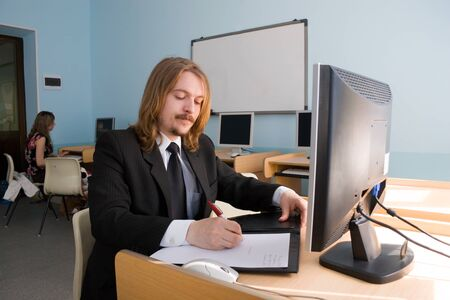 moneymaker: Young businessman is talking by mobile phone & also receives the information by computer.