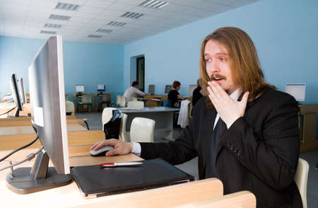 moneymaker: Young businessman surprised about computer information. Stock Photo