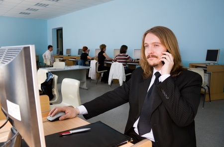 moneymaker: Young businessman is talking by mobile phone & receives the information by computer.