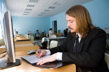 moneymaker: Young businessman writing some documents.