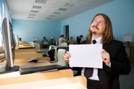 moneymaker: Young businessman is holding in hands clean sheet of a paper for your inscription. Stock Photo