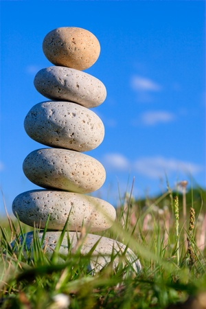 stack rock: Round stones lays on a grass. Blue sky on a background