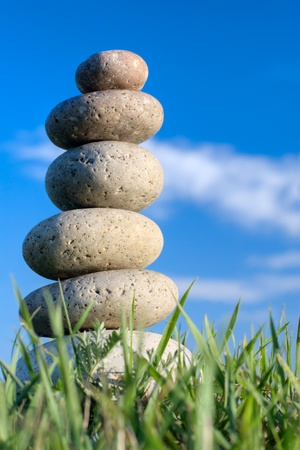 stack rock: Round stones lays on grass. Blue sky on a background Stock Photo