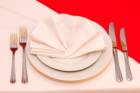 Restaurant. Dinner plate with napkin and a set of flatware. Stock Photo