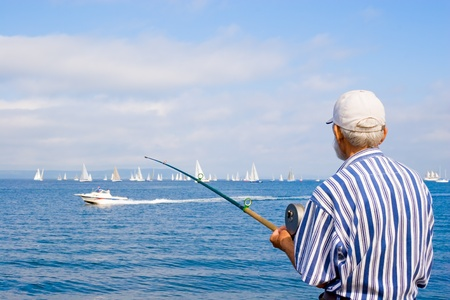 Old fisherman fishes and observes a yachts regatta