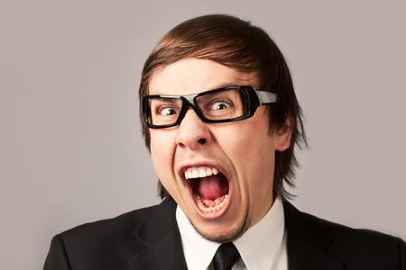 Close-up photo of screaming businessman, on a gray background