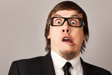 Close-up portrait of shocked businessman, hearing some news. On a gray background Stock Photo