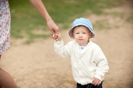 cute and serious boy holding his mother's hand during his promenade Stock Photo - 12903506