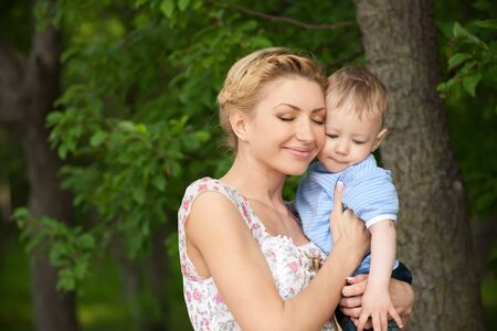 happy blond mom with her little son enjoying nature on a background of green leaves. Much of copyspace photo