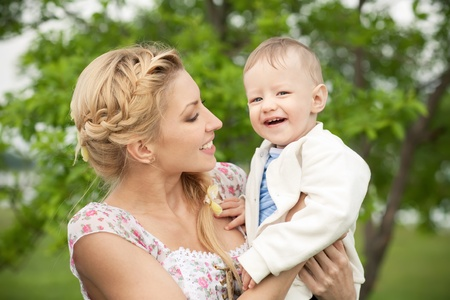 living moment: Happy blonde mom and son outdoors