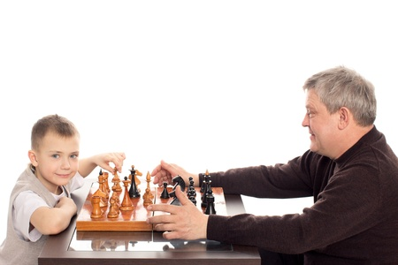 Grandfather and Grandson having a game of chess on a white background photo
