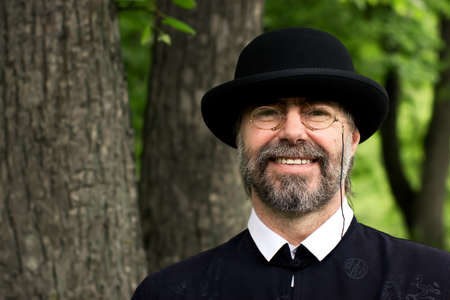 Portrait of a senior businessman smiling, wearing a suit and hat, as well as old fashion eyeglasses. Outdoors. photo