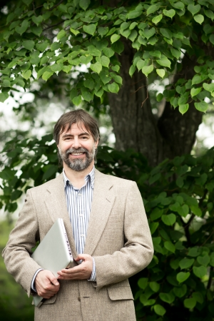 senior businessman holding notebook and smiling, outdoors photo