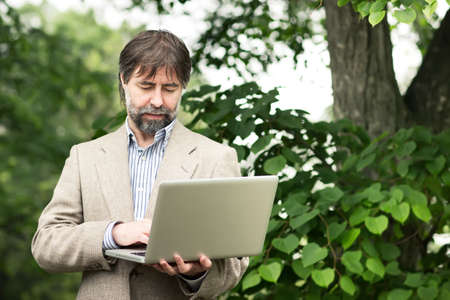 senior businessman working on a laptop, outdoors photo