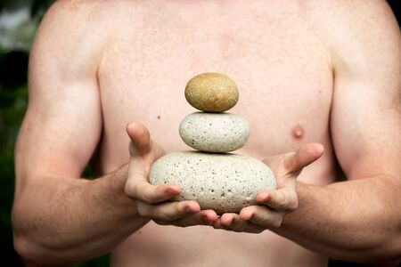 Strong athletic hands holding a pile of stones in balance. Get the balance concept. Stock Photo