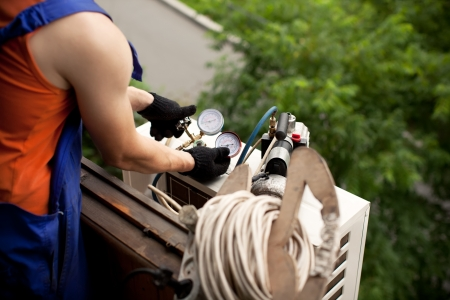 Air conditioning master preparing to install new air conditioner. removal of gases from the freon tubes Stock Photo