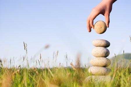 Verão. Construções a mão de alguém equilíbrio em uma grama. Imagens