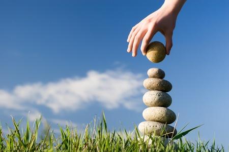 balanza: Verano. La mano de alguien construye el equilibrio sobre un c?sped.