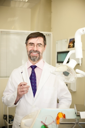 Portrait of happy middle-aged dentist in his cabinet, wearing lab coat, dentist mirror in his hand