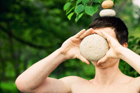Strong athletic man holding a pile of stones in balance on his head, covering his face with a stone. Get the balance concept.