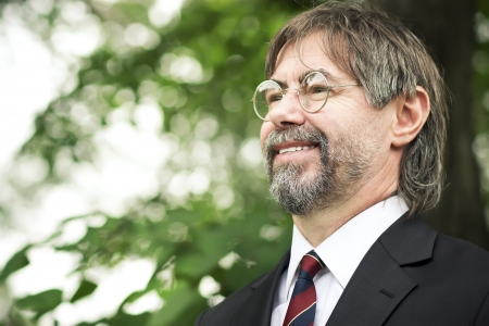 portrait of senior man with glasses, looking up against green wall and smiling Standard-Bild