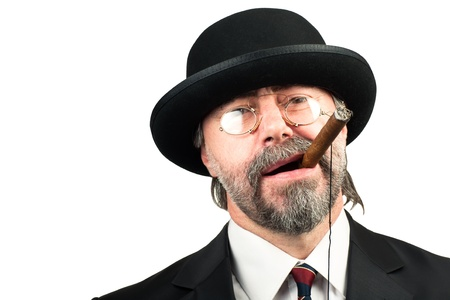 Closeup portrait of stilish man in a hat and in glasses smoking cigar and looking at you photo