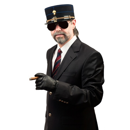 portrait of stilish man in   gendarme stile  hat and in sunglasses holding cigar, serious photo