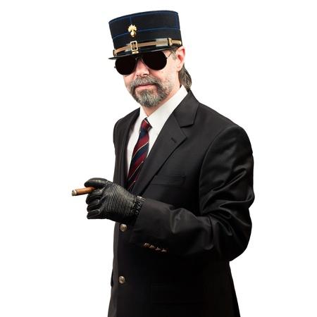 stilish: portrait of stilish man in   gendarme stile  hat and in sunglasses holding cigar, serious